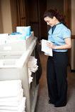 De stafmedewerker die van het huishouden de handhanddoek vouwt Royalty-vrije Stock Afbeeldingen