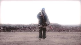 De stalker-landloper wandelt door de woestijn met gevonden dingen en een kruisboog De wereld wordt ondergedompeld in de post-kern stock videobeelden