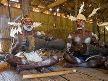 De stam van mensenasmat zit thuis en speelt op de trommel Stock Foto's
