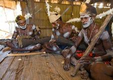 De stam van mensenasmat zit thuis en speelt op de trommel Royalty-vrije Stock Afbeeldingen