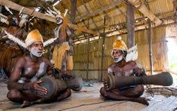 De stam van mensenasmat zit thuis en speelt op de trommel Royalty-vrije Stock Afbeelding