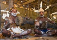 De stam van mensenasmat zit thuis en speelt op de trommel Stock Fotografie