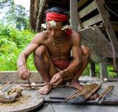 De stam van mensenmentawai bereidt vergift voor de pijlen voor de jacht voor Stock Foto's