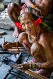 De stam van mensenmentawai bereidt vergift voor de pijlen voor de jacht voor Stock Fotografie
