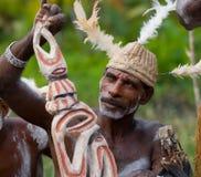De stam van strijdersasmat zit en snijdt een ritueel standbeeld Royalty-vrije Stock Foto's