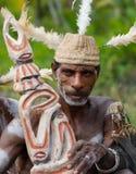 De stam van strijdersasmat zit en snijdt een ritueel standbeeld Stock Fotografie