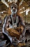De stam van strijdersasmat zit thuis in traditionele hoofddeksel en oorlogsverf Stock Afbeeldingen