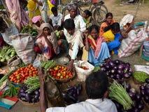 De stammen vrouwen verkopen groenten in wekelijkse markt Stock Foto