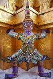 De Standbeelden van de demonbeschermer ondersteunend gouden Chedi in Wat Phra Kaew Stock Fotografie