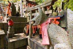 De standbeelden van de steenvos en velen kleine torii Stock Foto
