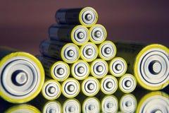De stapel gele aa-batterijen sluit omhoog abstracte kleurenachtergrond Stock Foto