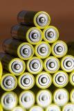 De stapel gele aa-batterijen sluit samenvatting omhoog gekleurde achtergrond Stock Fotografie