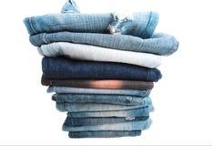 De stapel gevouwen kleren, jeans hijgt, donkerblauwe denimbroeken op witte achtergrond Royalty-vrije Stock Foto
