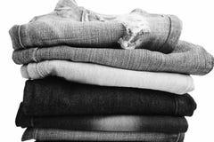 De stapel gevouwen kleren, jeans hijgt, donkerblauwe denimbroeken op witte achtergrond Stock Fotografie