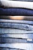 De stapel gevouwen kleren, jeans hijgt, donkerblauwe denimbroeken op witte achtergrond Royalty-vrije Stock Foto's
