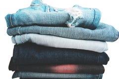De stapel gevouwen kleren, jeans hijgt, donkerblauwe denimbroeken op witte achtergrond Stock Afbeelding