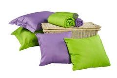 De stapel kleurrijke hoofdkussens en de verdraaide dekens op mand isoleren Stock Afbeeldingen