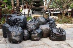 De stapel van afvalpartijen van plastic stapel van huisvuil de zwarte zakken op het openbare park van de vloergrond, velen dumpt  Royalty-vrije Stock Afbeeldingen