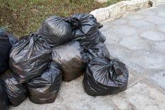 De stapel van afvalpartijen van plastic stapel van huisvuil de zwarte zakken op het openbare park van de vloergrond, velen dumpt  Royalty-vrije Stock Fotografie