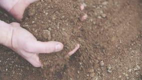 De stapel van de landbouwersholding van grond in handen Het onderzoeken van grond alvorens korrel te planten stock footage