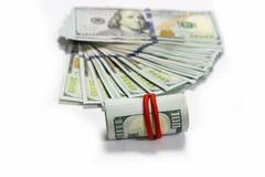 De stapel van dollarbankbiljetten en gerold op een witte achtergrond Royalty-vrije Stock Afbeeldingen