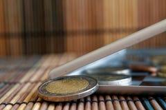 De stapel van Euro muntstukken in spiegel denkt na de portefeuille op houten bamboelijst ligt de brede hoekbenaming als achtergro Stock Foto