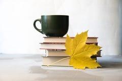 De stapel van het de herfstconcept boeken, coffe kop en esdoornbladeren stock afbeeldingen