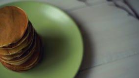 De Stapel van het pannekoekontbijt zoete pannekoeken op groene plaat op keukenlijst stock video