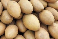 De stapel van het sapodillafruit in de markt stock afbeelding