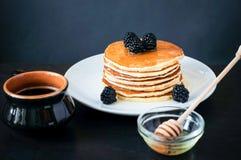 De Stapel van de hoekmening pannekoeken op witte plaat met braambes, een kop van koffie en een schotel met honing stock afbeeldingen