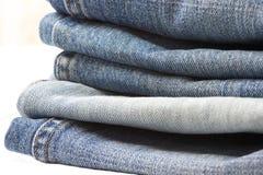 De Stapel van jeans op wit Stock Foto's