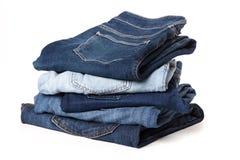 De stapel van jeansbroeken op witte achtergrond stock foto's