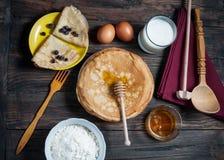 De stapel van omfloerst en ingrediënten voor het koken op een houten lijst Stock Foto's