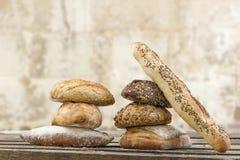 De stapel van verscheidene kleine multidie verschillende korrel vormde brood en baguette, met gehele zonnebloemzaden wordt bestro stock afbeeldingen