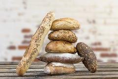 De stapel van verscheidene kleine multidie verschillende korrel vormde brood en baguette, met gehele zonnebloemzaden wordt bestro stock afbeelding