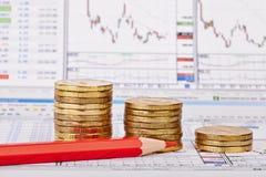 De stapels van neerwaartse trendmuntstukken, rood potlood, financiële grafiek als backgroun Stock Afbeeldingen