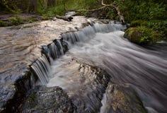 De stappen van de kalksteenrots leiden tot een waterval Stock Afbeeldingen
