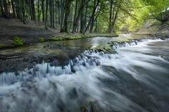 De stappen van de kalksteenrots leiden tot een waterval Stock Fotografie