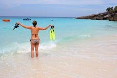 De status van de vrouw bij de strandholding snorkelt toestel Stock Afbeelding