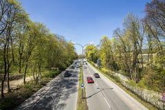 De stedelijke weg verdeelt de Engelse tuin in twee delen in Munic Stock Foto