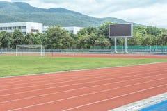 De Steeg van het atletiekspoor met oranje rubber wordt gemaakt dat stock afbeeldingen