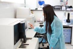 De steekproefbuizen van de laboratorium testen de hulplading voor coagulatie analyse en inputing gegevens aan coagulatiemachine stock afbeelding