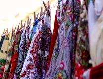 De steekproeven van de sjaals van heldere vrouwen hangen op een rij op een kabel stock afbeelding