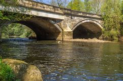 De steenbrug overspant de Rivier Aire in Cottingley royalty-vrije stock afbeelding