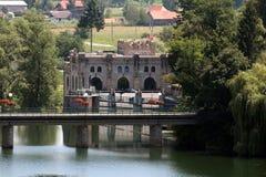 De steenbrug voor oude die dam verbond met de de steenbouw van de waterkrachtinstallatie als klein kasteel wordt gevormd royalty-vrije stock foto's
