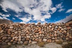 De steenmuur onder de bewolkte hemel Achtergrond Stock Afbeelding