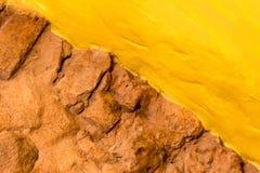 De steenmuur van de achtergrondtextuurbaksteen en gele geschilderde muur Stock Afbeeldingen