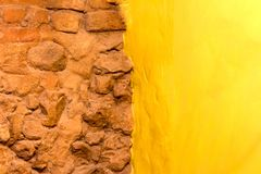 De steenmuur van de achtergrondtextuurbaksteen en gele geschilderde muur Royalty-vrije Stock Afbeeldingen