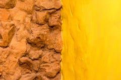 De steenmuur van de achtergrondtextuurbaksteen en gele geschilderde muur Stock Foto
