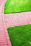 De steenweg van de tuin met gras, de Stoep van de Baksteen Stock Fotografie